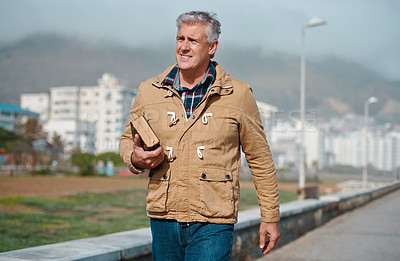 Buy stock photo Cropped shot of a handsome senior man walking with book in hand on the promenade near the beach