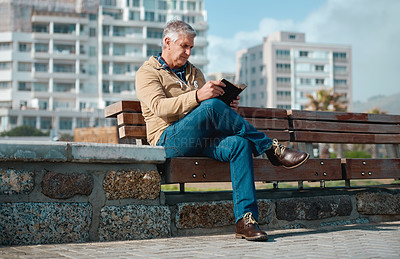 Buy stock photo Full length shot of a handsome senior man reading his book while sitting on a bench on the promenade at the beach