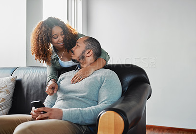 Buy stock photo Cropped shot of a beautiful young wife surprising her handsome husband while he's using a cellphone on the couch in the living room at home