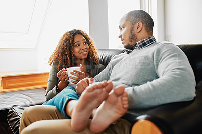 Buy stock photo Cropped shot of a young couple drinking coffee and chilling on the couch in the living room at home