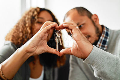 Buy stock photo Cropped shot of a young couple creating a heart frame with their hands and holding house keys in the living room at home