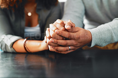 Buy stock photo Cropped shot of an unrecognizable couple compassionately holding hands at a table