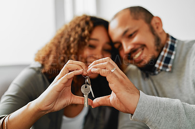 Buy stock photo Cropped shot of a young couple creating a heart frame with their hands and holding house keys while chilling at home