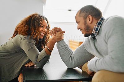Buy stock photo Cropped shot of a young couple arm wrestling on a table at home