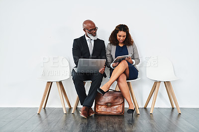 Buy stock photo Studio shot of a mature businessman and young businesswoman using wireless devices and talking while waiting