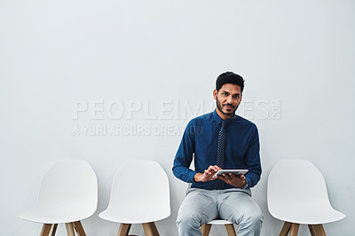 Buy stock photo Studio shot of a young businessman using a digital tablet while waiting