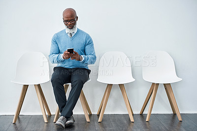 Buy stock photo Studio shot of a mature businessman using a mobile phone while waiting