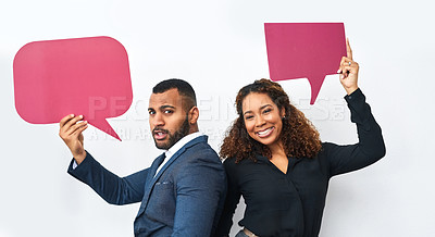 Buy stock photo Studio shot of a young businessman and businesswoman holding speech bubbles