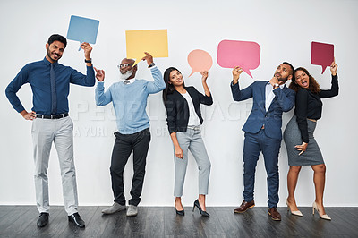Buy stock photo Studio shot of a group of businesspeople holding colorful speech bubbles while standing in line