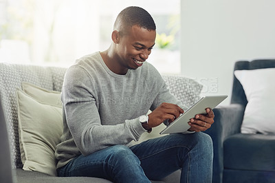Buy stock photo Cropped shot of a handsome young man using a tablet while chilling on the sofa in the living room at home