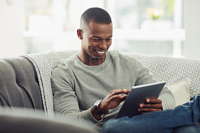 Buy stock photo Cropped shot of a handsome young man using a tablet while chilling on the sofa at home