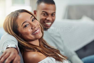 Buy stock photo Portrait of a young attractive couple chilling on the sofa at home