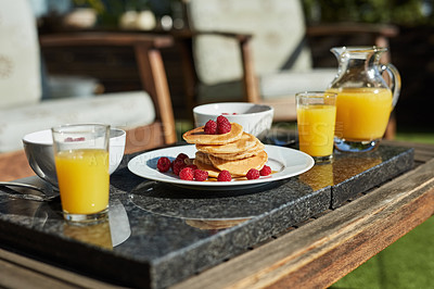 Buy stock photo Still life shot of pancakes and juice on a table outdoors