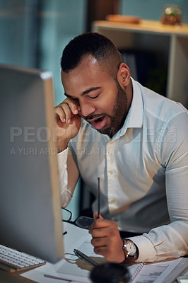 Buy stock photo Shot of a young businessman looking tired while working at his desk during late night at work
