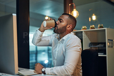 Buy stock photo Shot of a young businessman drinking coffee while working at his desk during a late night at wor