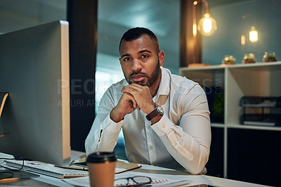 Buy stock photo Portrait of a young businessman working at his desk during a late night in a modern office