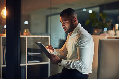Buy stock photo Shot of a young businessman using a digital tablet during a late night in a modern office
