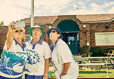Buy stock photo Shot of a group of senior women taking selfies during a game of bowls at a club