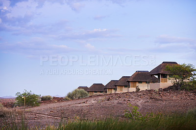 Buy stock photo Shot of a group of cottages situated inside of a luxurious holiday resort during the late afternoon hours