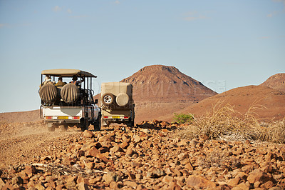 Buy stock photo Rearview shot of off road vehicles transporting guests through a holiday resort outside during the late afternoon hours