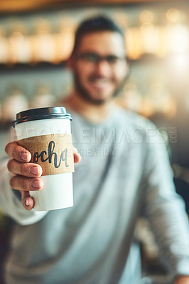 Buy stock photo Shot of a barista holding a cup of coffee in a cafe