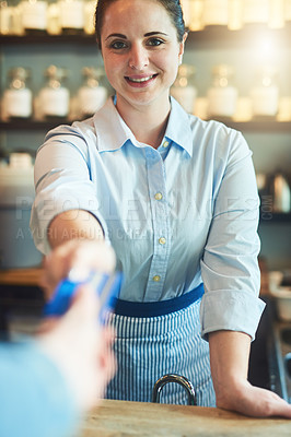 Buy stock photo Portrait of a young woman receiving a credit card payment from a customer in a cafe