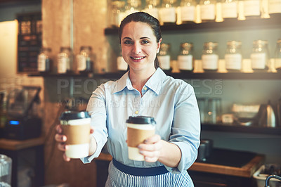 Buy stock photo Portrait of a young barista holding cups of coffee in a cafe