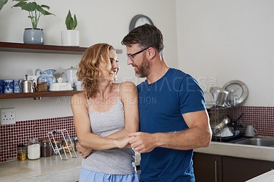 Buy stock photo Shot of a happy middle aged couple bonding in the kitchen at home
