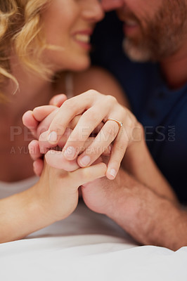 Buy stock photo Cropped shot of a happy middle aged couple holding hands and relaxing in bed together
