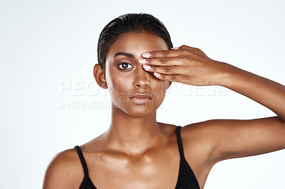 Buy stock photo Studio shot of a beautiful young woman covering her eye against a light background