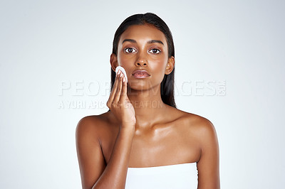 Buy stock photo Studio shot of a beautiful young woman wiping her face with a cotton disc against a light background