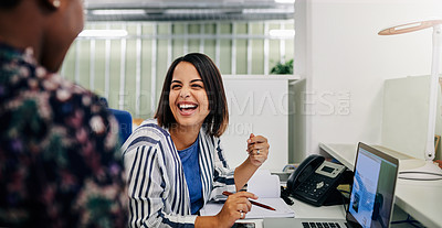 Buy stock photo Shot of a young businesswoman laughing while talking with a coworker in a modern office