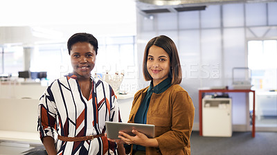 Buy stock photo Portrait of two confident young businesswomen working together in a modern office