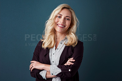 Buy stock photo Studio shot of a beautiful young businesswoman posing against a blue background