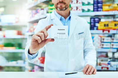 Buy stock photo Cropped shot of an unrecognizable mature male pharmacist showing you a package while working in a pharmacy