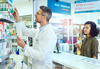 Buy stock photo Cropped shot of a handsome mature male pharmacist helping a female customer in the pharmacy