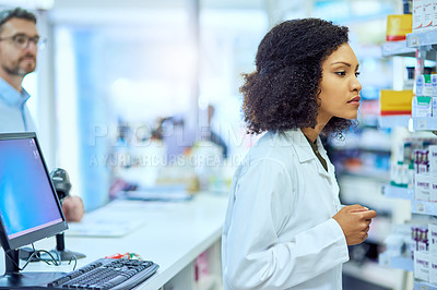 Buy stock photo Cropped shot of an attractive young female pharmacist looking for medication in a pharmacy