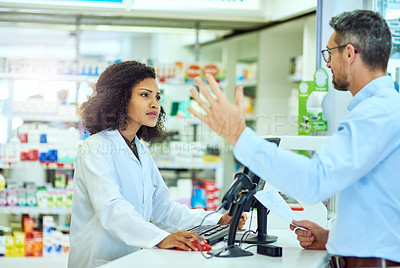Buy stock photo Cropped shot of an attractive young female pharmacist helping a male customer in the pharmacy