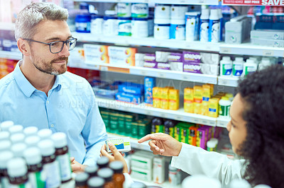 Buy stock photo High angle shot of a handsome mature male customer buying medication in a pharmacy