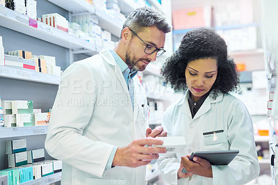Buy stock photo Shot of a mature man and young woman using a digital tablet together while working in a pharmacy