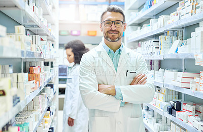 Buy stock photo Portrait of a confident mature man working in a pharmacy with his colleague in the background