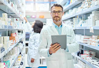 Buy stock photo Shot of a mature man using a digital tablet to do inventory in a pharmacy