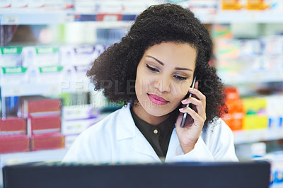 Buy stock photo Shot of a young woman using a computer and mobile phone at the counter of a pharmacy
