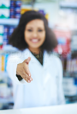 Buy stock photo Shot of a young woman extending her arm for a handshake at the counter of a pharmacy