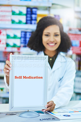 Buy stock photo Shot of a young woman showing a self medication sign at the counter of a pharmacy