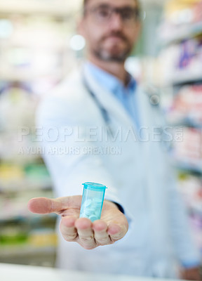 Buy stock photo Shot of a mature man extending his arm to show a bottle of pills at a pharmacy
