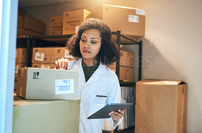 Buy stock photo Shot of a young woman using a digital tablet while doing inventory in the storeroom of a pharmacy