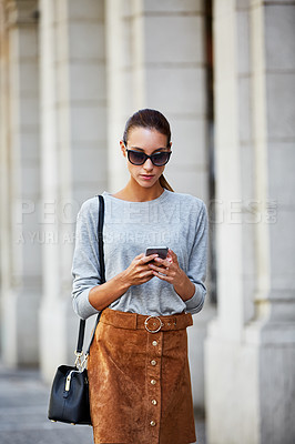 Buy stock photo Cropped shot of a young woman walking through the city