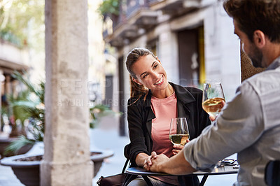 Buy stock photo Shot of a couple having wine outside at a restaurant