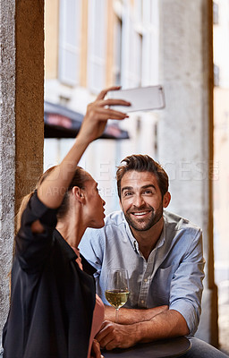 Buy stock photo Shot of a happy couple taking a selfie while sitting outside at a restaurant